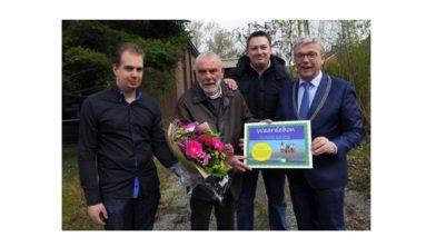 De heer Haaijer, geflankeerd door zijn zoons, ontvangt de prijs uit handen van burgemeester Koos Wiersma van De Marne
