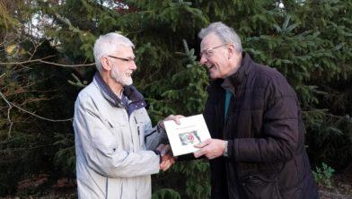 Paul Datema (links) ontvangt het jubileumboek.