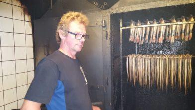 Gaele Postma legt een groep bezoekers de fijne kneepjes van het palingroken uit.