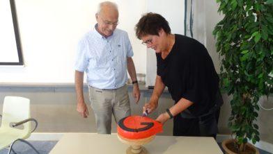 Jan van 't Zand en Gerrie de Roo snijden de taart aan.