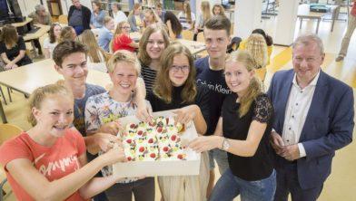 Gedeputeerde Tjisse Stelpstra komt prijs aan de leerlingen overhandigen die naar milieusymposium in Denemarken gaan.