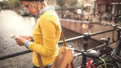 Photo of a young woman using her mobile phone for finishing her work, while walking the sunny streets of Amsterdam