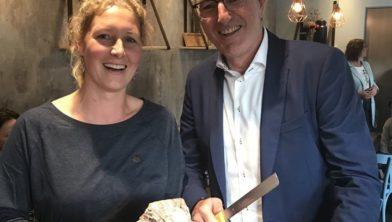 Giske Warringa namens DAJK en Gedeputeerde Henk Jumelet bij het aansnijden van een Dubbel Drents brood tijdens de Dutch Agri Food Week.